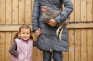 A woman and a child, holding a black and white chickenの写真素材 [FYI02245739]