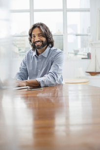 A young man with a beard seated at a table with a laptop.の写真素材 [FYI02245775]