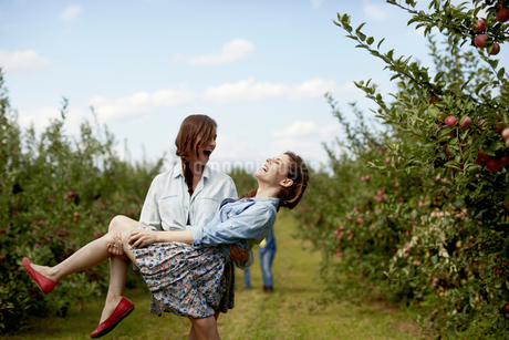 Two young women laughing, one carrying the other.の写真素材 [FYI02245875]