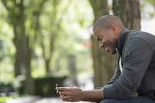 A man in a grey zipped sweatshirt using his smart phoneの写真素材 [FYI02245886]