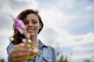 A young woman holding out a wild flower with pink petals.の写真素材 [FYI02245890]