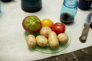 A table with a cloth, and plate with potatoes and tomatoes.の写真素材 [FYI02245897]