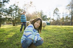 Two children at an animal sanctuary in a group of sheepの写真素材 [FYI02245899]