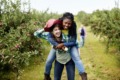 Young woman giving another a piggyback in a fruit orchard.の写真素材 [FYI02245910]
