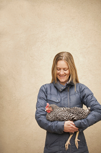 A woman wearing a grey coat and holding a chicken.の写真素材 [FYI02245916]