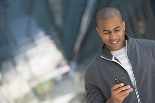 City park. A man in a grey sweatshirt using his smart phoneの写真素材 [FYI02245941]