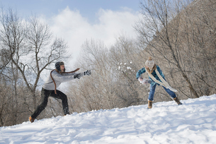 A couple having a snowball fight.の写真素材 [FYI02245943]