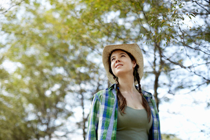 A girl in a straw hat walking in the woods.の写真素材 [FYI02245955]