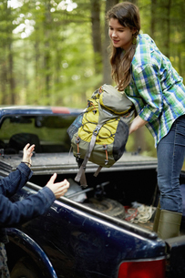 A young woman unloading rucksacks from a pickup truck.の写真素材 [FYI02245969]