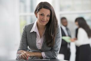 A woman in a grey jacket, using a digital tablet.の写真素材 [FYI02245991]