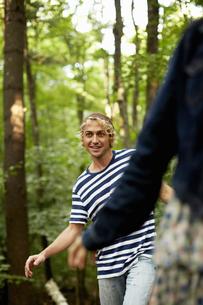 Two people walking along a fallen tree trunk in the woods.の写真素材 [FYI02246112]
