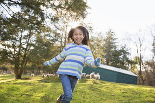 Young girl in a field of sheep at animal sanctuary.の写真素材 [FYI02246172]