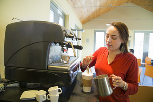 A young woman pouring frothed milk onto a cup of coffee.の写真素材 [FYI02246212]