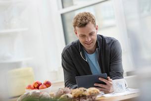 A man in a sweatshirt top using a digital pad.の写真素材 [FYI02246283]