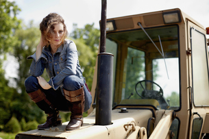 A young woman in denim jacket on the hood of a tractor.の写真素材 [FYI02246308]