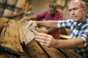 A man measuring and checking planks of wood for recycling.の写真素材 [FYI02246325]