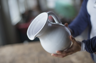 A woman holding a white pottery jug in an antique storeの写真素材 [FYI02246504]