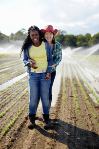 Two young women with a sprinkler system working in a field.の写真素材 [FYI02246508]
