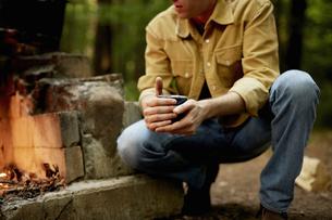 A man kneeling by a blazing camp fire.の写真素材 [FYI02246536]