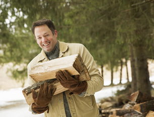 A man outdoors carrying an armful of logsの写真素材 [FYI02246631]