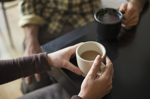 A coffee shop. Two people sitting holding coffee cups.の写真素材 [FYI02246644]