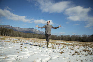 A man in a cable knit jumper in a snowy rural landscape.の写真素材 [FYI02246666]