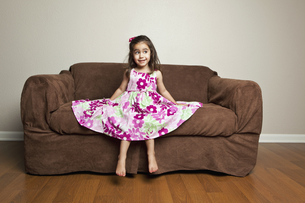 A 3 year old girl with brown hair sitting on a brown sofa.の写真素材 [FYI02246709]