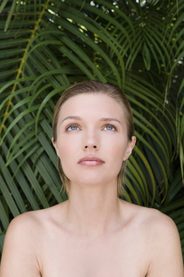 A young woman with bare shoulders, looking upwards. Tropical plants in the background.の写真素材 [FYI02246733]