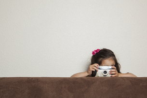 three year old girl with a toy camera, taking a picture.の写真素材 [FYI02246740]