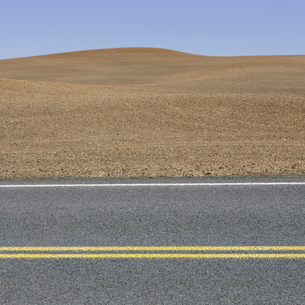 A road through the farming landscape of ploughed fieldsの写真素材 [FYI02246744]