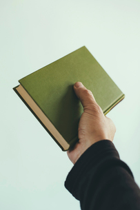 A man's hand holding an old green hardback book.の写真素材 [FYI02246765]