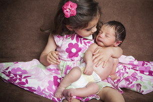 A young girl holding a newborn baby sibling.の写真素材 [FYI02246770]
