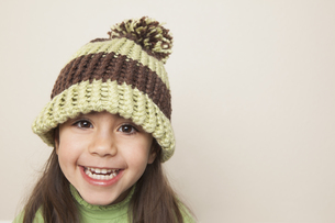 A young child with long brown hair wearing a knitted hatの写真素材 [FYI02246772]