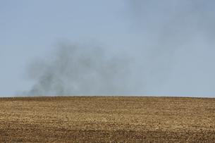 Smoke rising above a ridge, viewed across a ploughed fieldの写真素材 [FYI02246778]