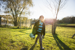 A young boy in an animal paddock with a bucket of feedの写真素材 [FYI02246810]