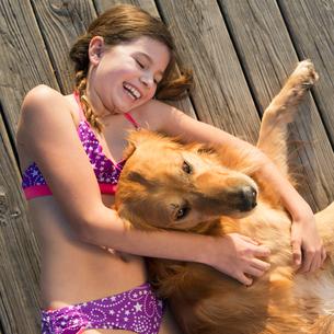 A girl in a bikini lying beside a golden retriever dog, viewed from above.の写真素材 [FYI02246815]