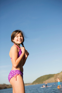 A young girl on a jetty with paddleboarders in the background.の写真素材 [FYI02246848]