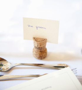 Close up of a place setting at the top table at a wedding banquet. An upside down cork with name tagの写真素材 [FYI02246857]