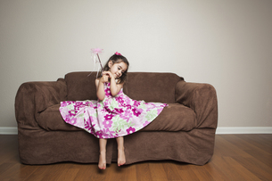 A 3 year old girl with a skirt spread out, waving a wand.の写真素材 [FYI02246869]