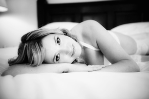 A woman wearing white lace underwear lying on a bed.の写真素材 [FYI02246871]