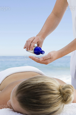 The beach. A young woman having a massage.の写真素材 [FYI02246876]