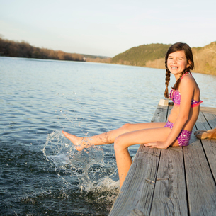 A girl in a bikini sitting on a jetty with her feet in the water.の写真素材 [FYI02246882]