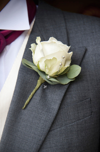 A groom in a grey jacket and white shirt, with a white rose boutonniere, in his buttonhole.の写真素材 [FYI02246884]