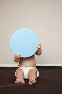 A young 8 month old baby boy behind a large blue disc.の写真素材 [FYI02246901]