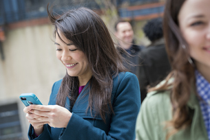 A woman checking her turquoise smart phoneの写真素材 [FYI02246922]