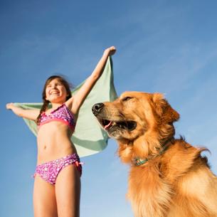 A girl in a beach towel with a golden retriever dog.の写真素材 [FYI02246923]