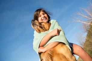 A girl in a beach towel with a golden retriever dog.の写真素材 [FYI02246925]
