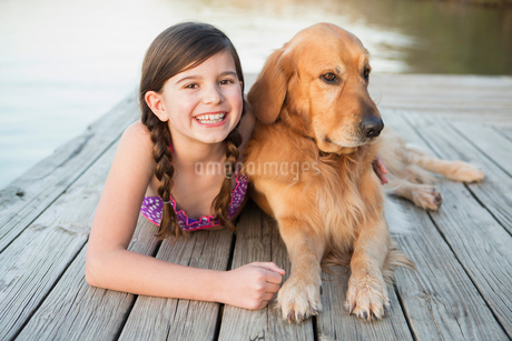 A young girl and a golden retriever dog lying on a jetty.の写真素材 [FYI02246939]