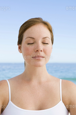 A young woman seated on the beach in a relaxed pose, with her eyes closed.の写真素材 [FYI02246958]