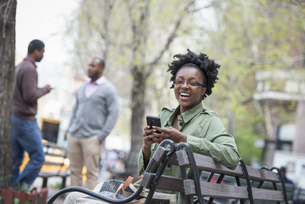A woman on a bench checking her phoneの写真素材 [FYI02246987]